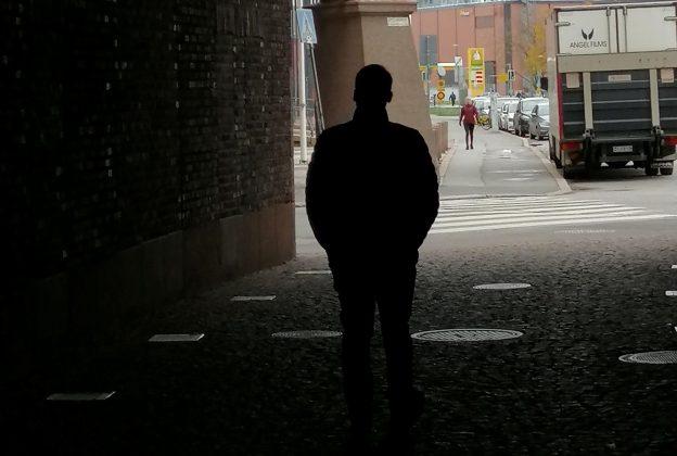 Mies kävelee pimeästä porttikongista kohti valoa ja kadun vilskettä.