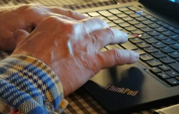 Vanhemman ihmisen kädet tietokoneen näppäimistöllä.