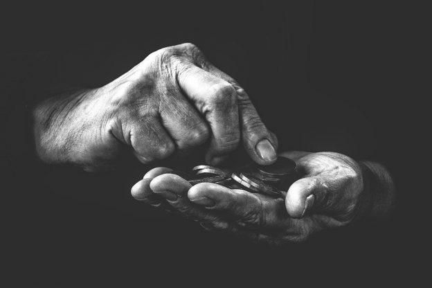 Kädet, joista toisessa kolikoita, joita toisen käden sormilla lasketaan.