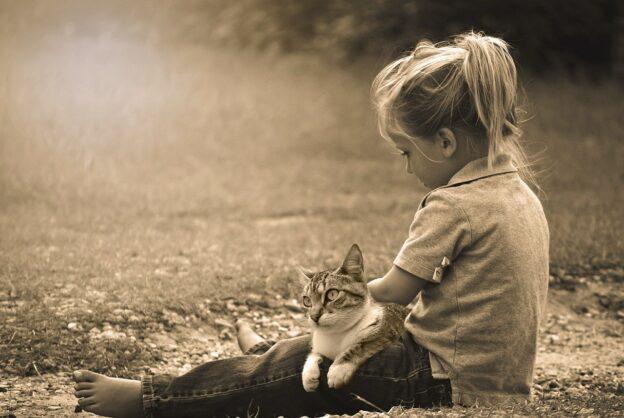Lapsi istuu nurmikolla kissa sylissään.