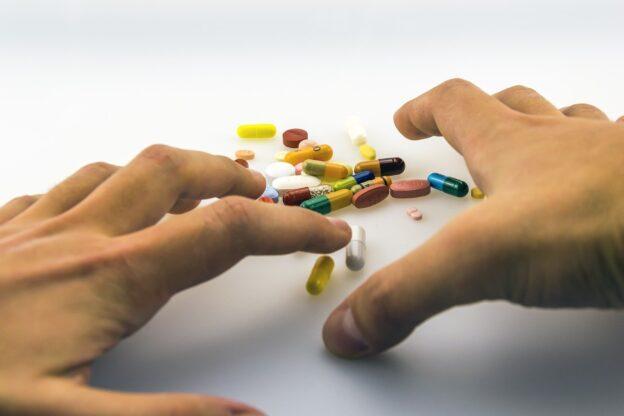 Kaksi kättä ja niiden välissä pöydällä lääkkeitä.