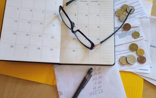 Kalenteri, silmälasit, kolikoita, vihossa laskelma rahojen riittämisestä