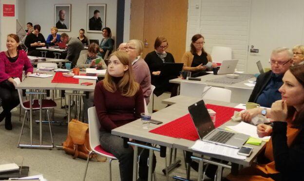 Ihmisiä istuu kuuntelemassa kokoustilassa.