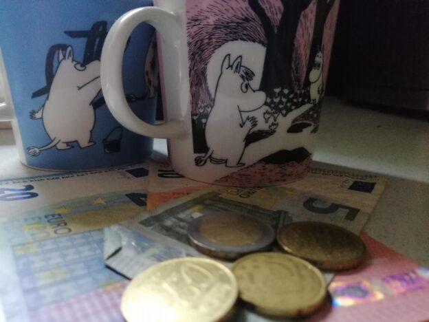 Kaksi mukia edessä seteleitä ja kolikoita