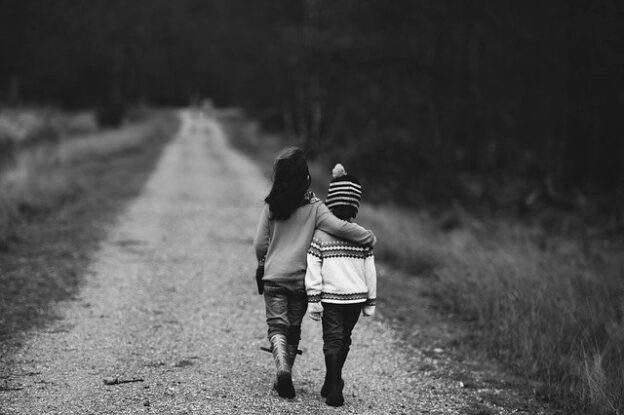 Kaksi lasta hiekkatiellä, isomman lapsen käsi toisen harteiden ympärillä.
